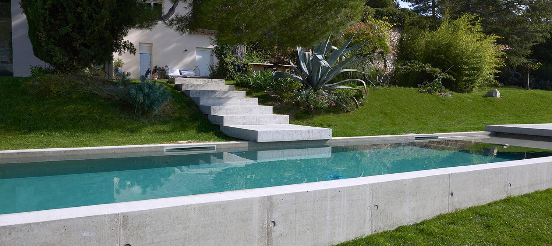 piscine en béton brut semi-enterrée