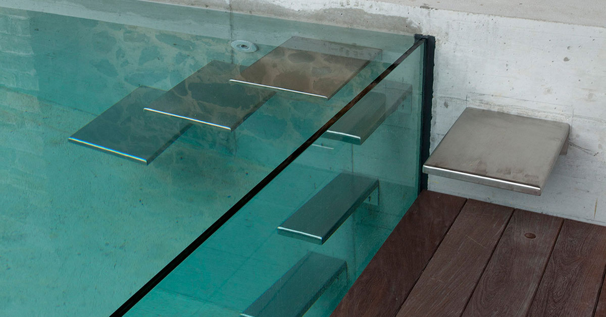 piscine à parois vitrées avec escalier inox