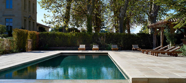 piscine à débordement en béton brut avec bains de soleil
