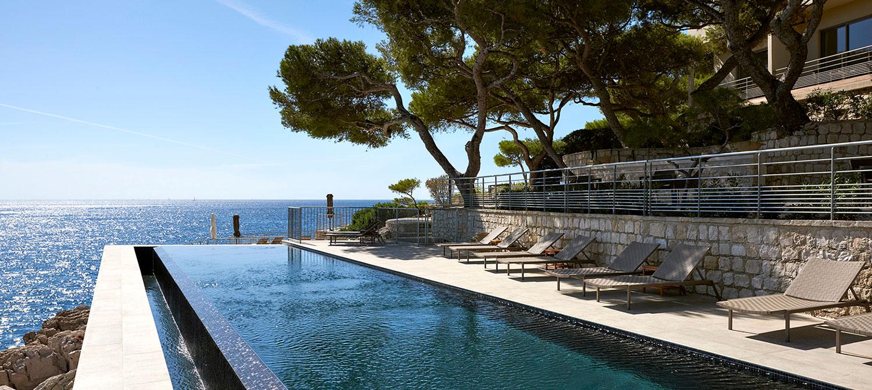 piscine à débordement avec bains de soleil vue sur mer